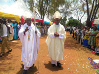 Bishop Kirabo (left holding a crosier)  with Rt. Rev. Lambert Bainomugisha,  the Auxiliary Bishop of Mbarara  Archdiocese during his ordination  ceremony as a bishop last year