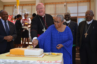 H.E. Most Rev. Charles Daniel Balvo the Apostolic Nuncio  to Kenya and South Sudan cutting the cake to mark the  Anniversary of Pope Francis. He is assisted by Kenya's  First Lady Margaret Kenyatta