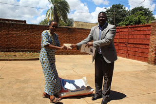 Catholic Secretariat's Director of Finance and Administration handing over cash to Sister Massawe as contributed by Catholic Secretariat's staff