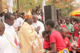 Archbishop Msusa Receives gifts from children  during the Celebrations of the Holy  Childhood in the Archdiocese of Blantyre
