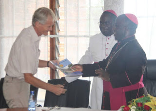 Archbishop Msusa Present a copy of the Strategic Framework to one of the donor partner, Dan from Church Aid