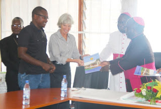 Archbishop Msusa presents a copy to CRS Catholic Director and Trocaire representative